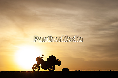 silhuetted touring motorcykel ved solnedgang