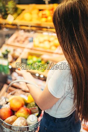 kvindelig kunde mod frugtsektion i fodevarebutik