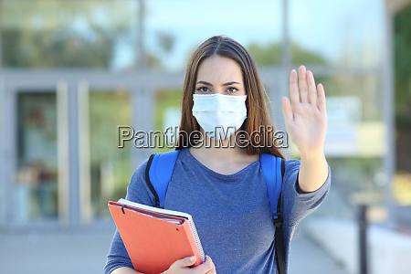studerende med en maske gestikulerende stop
