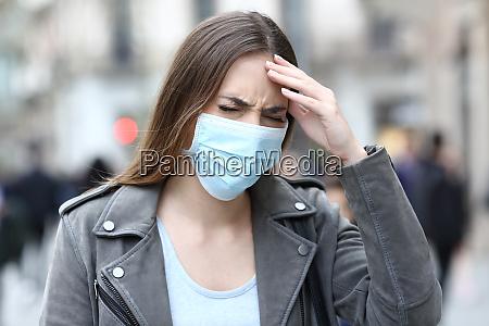 kvinde med beskyttende maske lider hoved