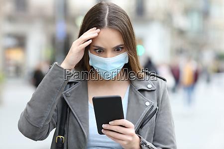 bekymret kvinde med maske tjekker telefon