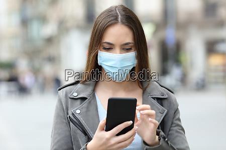 alvorlig pige med maske tjekker hendes