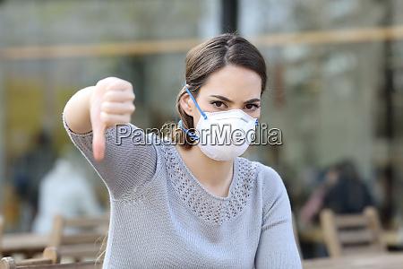 kvinde gor thumbs down ifort maske