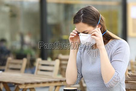 kvinde tager beskyttelsesmaske pa cafeterrasse