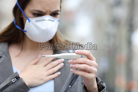 kvinde med beskyttende maske kontrol termometer