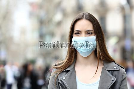 alvorlig kvinde med maske kigger vaek