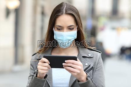 kvinde med maske ser video pa