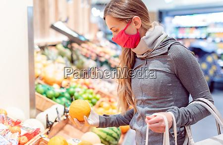 kvinde shopping i supermarkedet under coronavirus