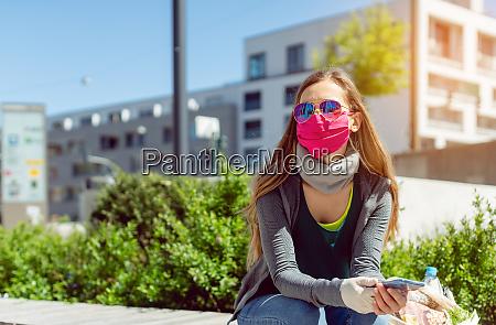 kvinde med ansigtsmaske sidder udenfor som