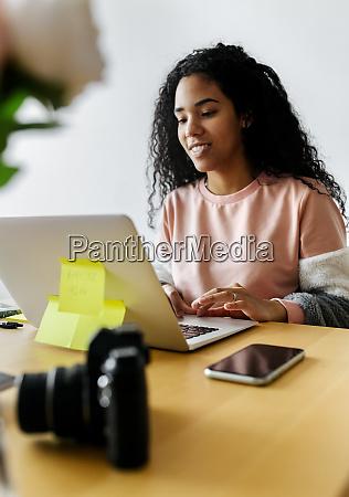ung kvinde der arbejder hjemmefra ved