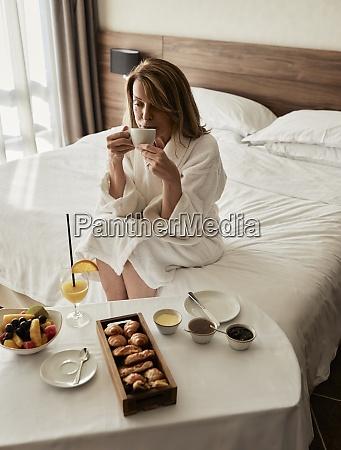 blond senior kvinde drikker kaffe mens