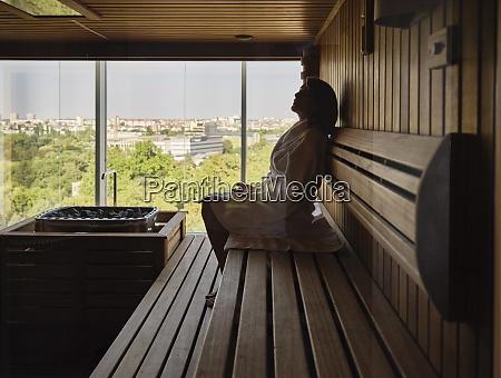 senior kvinde sidder pa trae sauna