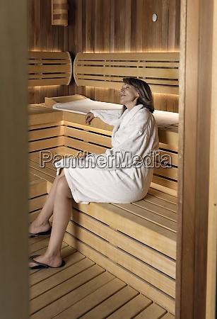 tankevaekkende kvinde ifort badekabe sidder pa